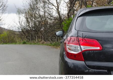Back view of new black car on rural road. Autumn season. - stock photo