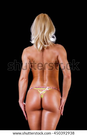 Back view of nude sporty femaleisolated on a black background.