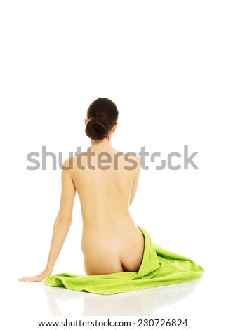 Back view of nude woman sitting on a towel. - stock photo