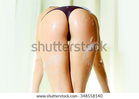 Back view of one attractive passionate young brunette sexy naked woman with wet long curly hair straight body and buttocks in panties standing in bath tab water black and white, vertical picture - stock photo
