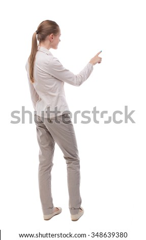 Back view of  pointing woman. beautiful girl. Rear view people collection.  backside view of person.  Isolated over white background.  A girl in a white jacket is pointing into the distance. - stock photo