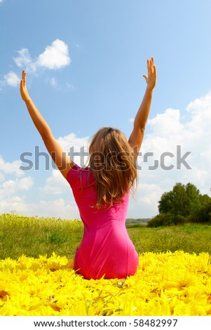 Back view of pretty girl seated on sunflowers and enjoying summer day