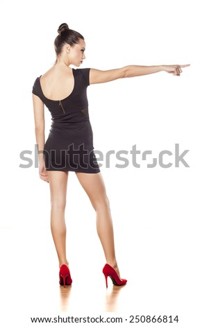 Back view of pretty young woman in short black dress, pointing