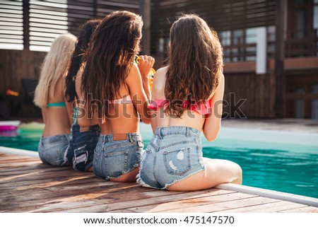 Back view of pretty young women with long hair sitting and drinking cocktails near swimming pool