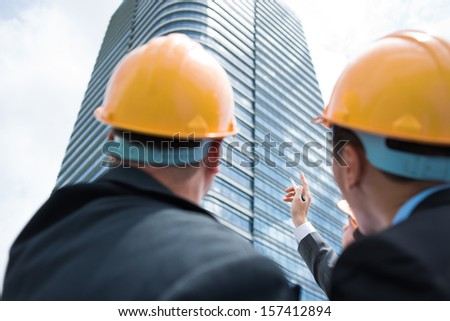 Back view of professional constructor workers discussing something while one of them pointing at something on the foreground - stock photo