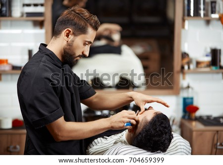 back view of professional hairstylist in black uniform caring and cutting bread for young man