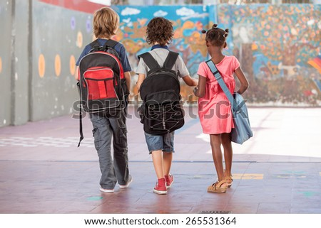 Back view of school mates walking on the schoolyard. Multi ethnic classroom. - stock photo