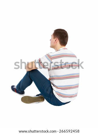 Back view of seated handsome man in t-shirt and jeans looking up. Rear view people collection. Backside view of person. Isolated over white background. - stock photo