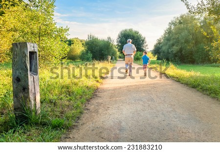 Back view of senior man with hat and happy child running on a nature path. Two different generations concept. - stock photo