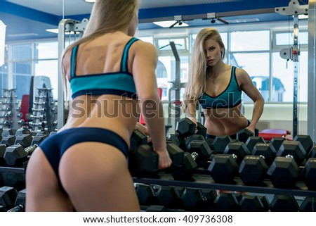 Back view of sexy girl near rack with dumbbells