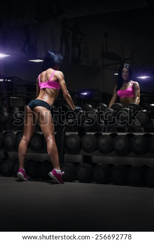 back view of sexy young brunette woman resting in the gym and leaning on row of dumbbells. Fitness girl in gym in a blue sport wear - stock photo