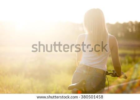 Back view of sporty beautiful young woman on bike wearing casual white tank top and denim shorts in bright sunshine on summer day, copy space - stock photo