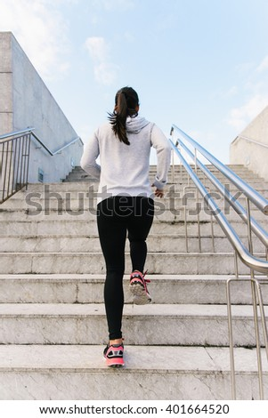 Back view of sporty urban woman running and climbing stairs. Female athlete on hiit workout. - stock photo