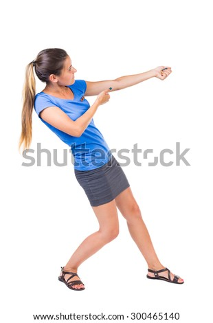 back view of standing girl pulling a rope from the top or cling to something. girl  watching. Isolated over white background. Girl in a gray skirt and blue shirt pulling the rope something heavy right - stock photo