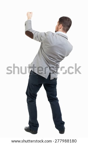 back view of standing man pulling a rope from top or cling to something.  Rear view people collection.  Isolated over white background. Businessman pulling a rope on top of something. - stock photo