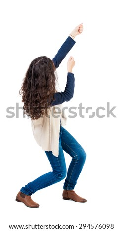 back view of standing woman pulling a rope from the top or cling to something.  Rear view people collection.   Isolated over white background. Girl in sheepskin jerkin pulling a rope from the top. - stock photo
