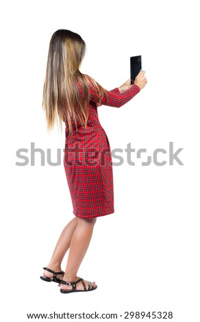 back view of standing young beautiful  girl with tablet computer in the hands of. girl  watching. Isolated over white background. Long-haired girl in a red plaid dress takes tablet something. - stock photo