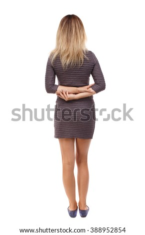 back view of standing young beautiful  woman.  girl  watching. Rear view people collection.  backside view of person. Hands clasped behind the back of the girl in a brown dress looks ahead.