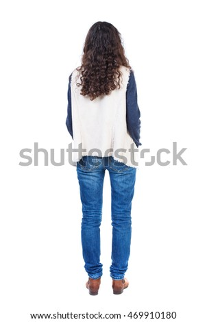 back view of standing young beautiful  woman.  girl  watching. Rear view people collection.  backside view of person. Long-haired girl with curly hair standing with his hands in his pockets.