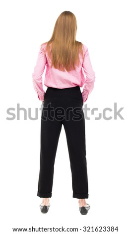 back view of standing young beautiful woman. girl watching. Rear view people collection. backside view person. Isolated over white background. girl in pink shirt stands with his hands in his pockets