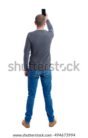 back view of standing young man  and using a mobile phone. girl watching. Rear view people collection.  backside view of person.  Isolated over white background. A guy in a gray sweater photographs