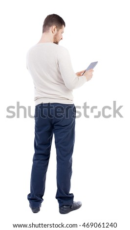 back view of standing young man with tablet computer in the hands of. Rear view people collection.  backside view of person.  Isolated over white background. The bearded man in a white warm sweater