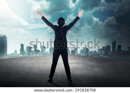 Back view of successful business woman on the rooftop looking the sky - stock photo
