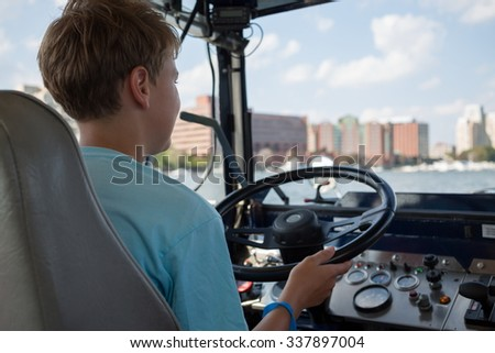 Back view of the boy is sitting at an amphibia car. - stock photo