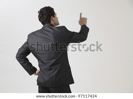 back view of the businessman pointing - stock photo