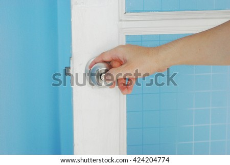 Back view of the hand's man is holding and locking stainless steel round ball door with white blue house - stock photo