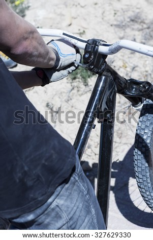 back view of the hands of a BMX cyclist adjusting the handlebar of the BMX bike - focus on the middle of the handlebar