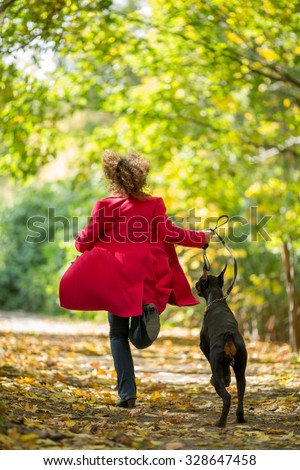 Back view of the woman in a red coat is running with a dobermann in wood. - stock photo