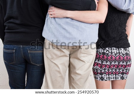 Back view of three people one man and two women looking. - stock photo
