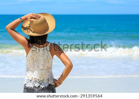 Back view of Travel asia woman with hat looking out of sea on a beach in summer, Koh Samet, Thailand - stock photo