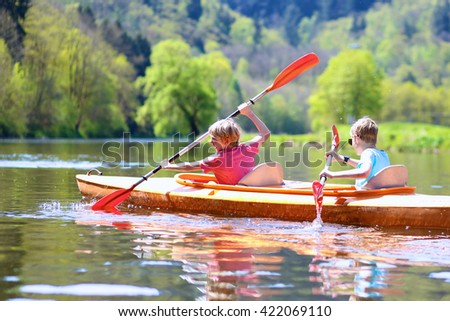 Back view of two boys kayaking on the river. Active happy friends, teenage schoolboys, having fun together enjoying adventurous experience with kayak on a sunny day during summer vacation