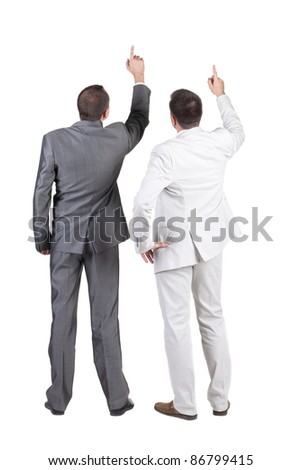 Back view of two businessman pointing at wall. rear view. Isolated over white .