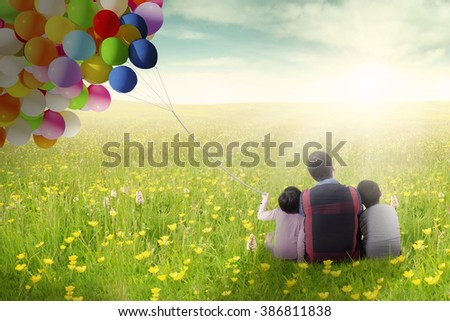 Back view of two children sitting on the grass with their father while holding balloon, shot at springtime - stock photo