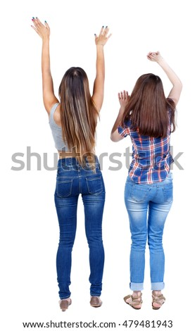 Back view of two dancing young women. Isolated over white background. Two young girls in jeans happily waving their hands.