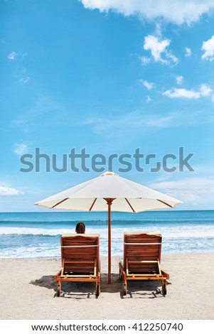 Back View Of Two Deckchairs, Sun Loungers Under Umbrella On Sand Beach. Woman Relaxing On Lounge Chairs Under Tent By Sea. Girl Enjoying Summer Holidays Vacations At Tropical Resort. Summertime Relax