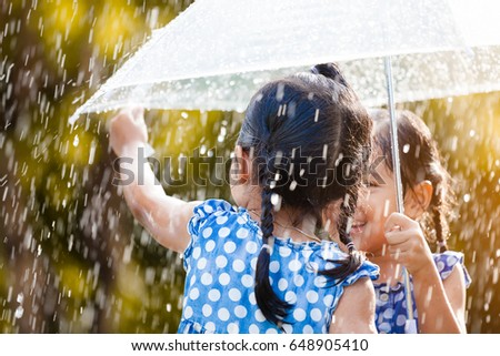 Back view of two happy asian little girls with umbrella having fun to play with the rain together in vintage color tone