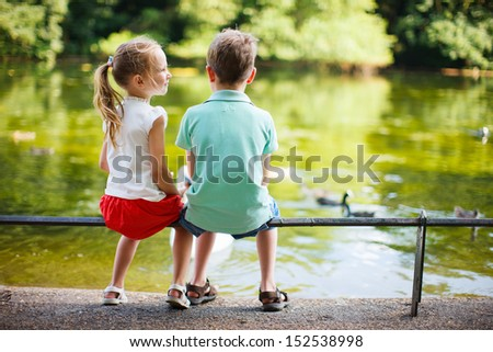 Back view of two kids outdoors at park - stock photo