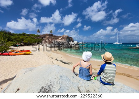 Back view of two kids sitting on granite boulder and enjoying beautiful scenery of The Baths beach area major tourist attraction at Virgin Gorda, British Virgin Islands, Caribbean - stock photo