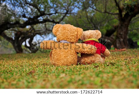 Back view of two teddy bears sitting in the garden with love. Concept about love and relationship. - stock photo