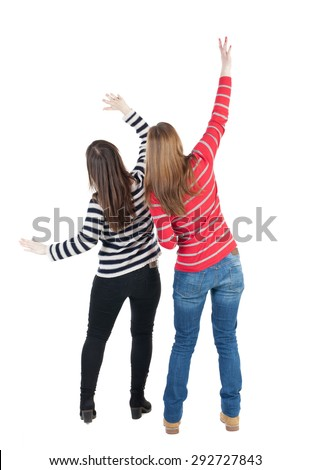 Back view of two young  brunette standing woman  l . beautiful girl friends  discuss. Rear view people collection.  Isolated over white background. Two girls at a concert waving their arms