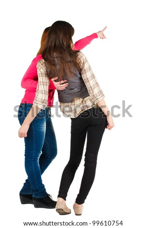 Back view of two young woman (brunette and blonde) pointing at wall . beautiful girl friends  showing gesture. Rear view. Isolated over white background. - stock photo