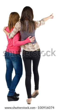 Back view of two young woman (brunette and blonde) pointing at wall . Rear view people collection.  backside view of person. beautiful girl friends  showing gesture. Isolated over white background.