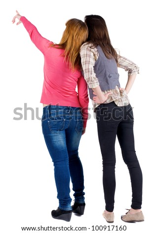 Back view of two young woman (brunette and blonde) pointing at wall . Rear view people collection.  backside view of person. beautiful girl friends  showing .   Isolated over white background. - stock photo