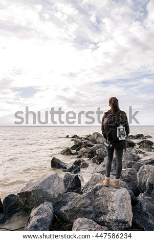 Back view of unrecognizable backpacker on rocky shore against of cloudy sky.Copy space