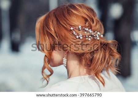 Back view of unrecognizable young woman with red hair in white wedding dress and wreath over blurred outdoors background - stock photo