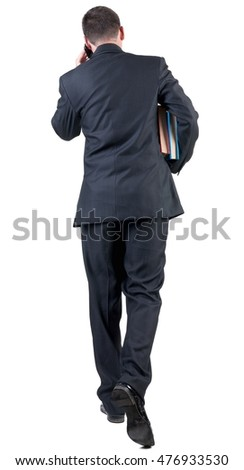 back view of walking  business man with books. going young guy in black suit talking on mobile phone. Isolated over white background. Rear view people collection. backside view of person